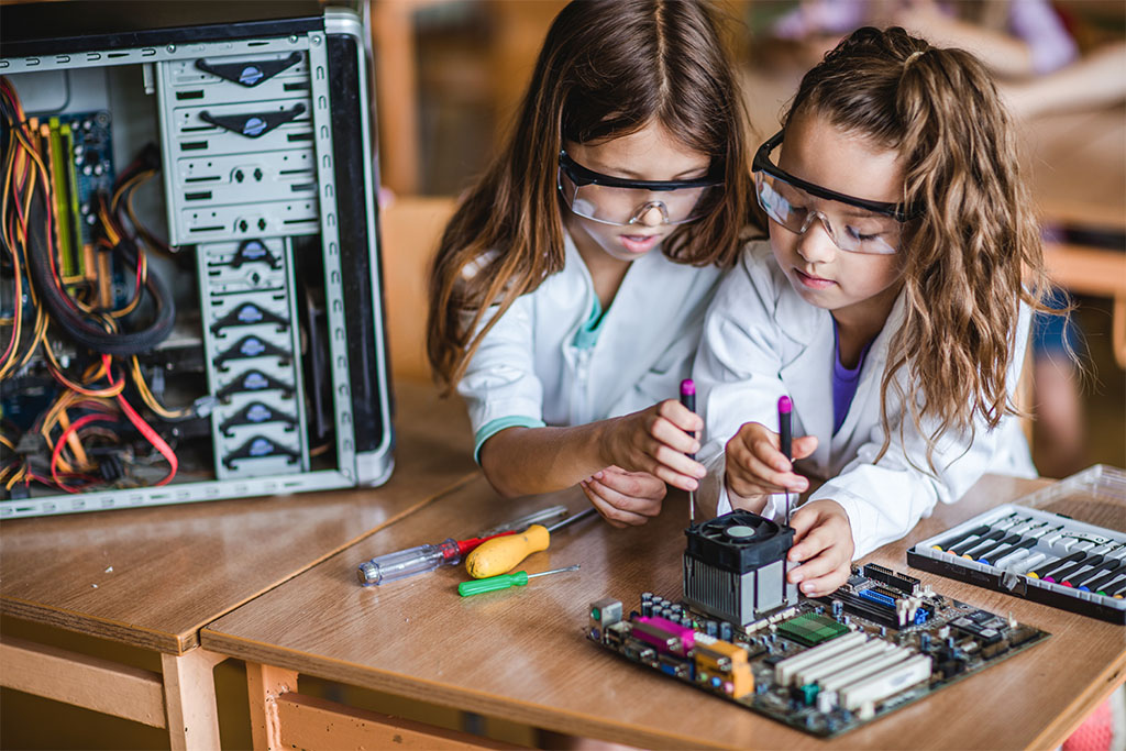 Elementary schoolgirls repairing computer mother board during a class in the classroom.