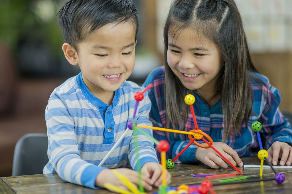 An East Asian brother and sister wearing plaid and stripes smile as they play with building toys in an indoor, homeschool environment.