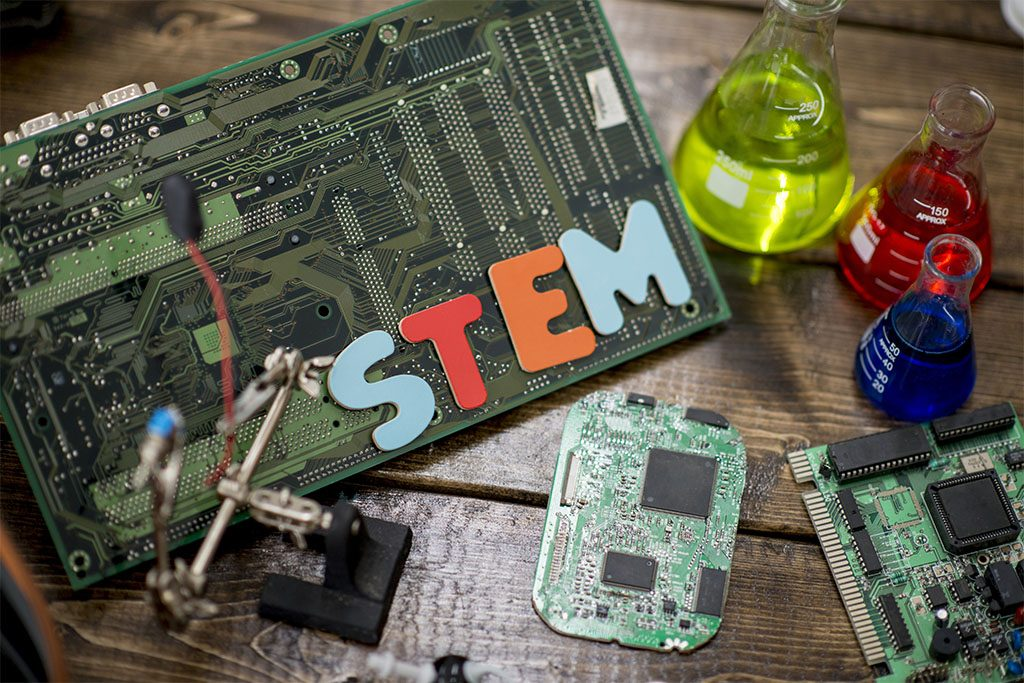 """A variety of science-related materials are displayed on a table, including: a large motherboard, science flasks filled with colorful liquids, and various computer parts. """"STEM"""" is spelled out in colorful letters."""