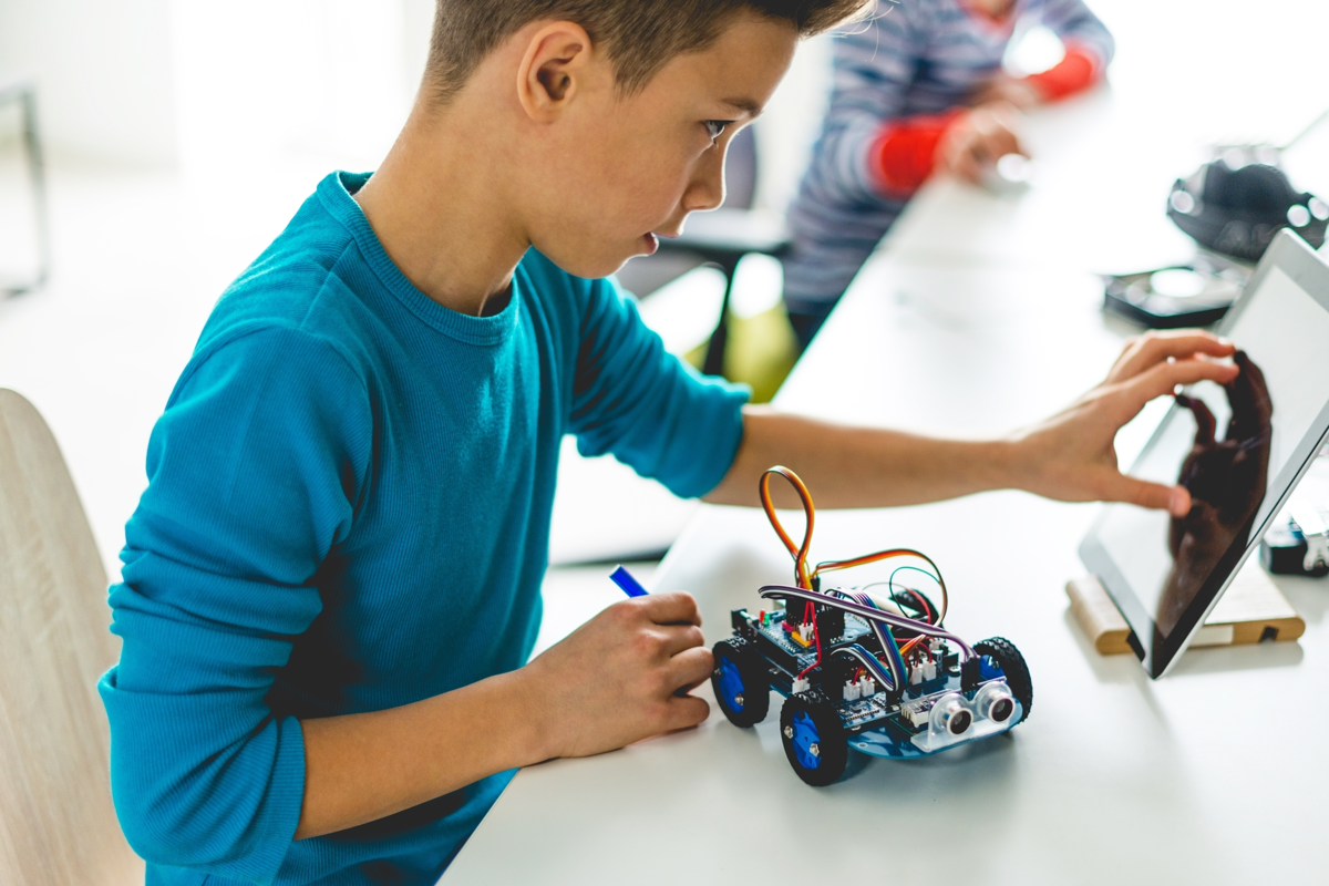 Boy learning about robots in a public library STEM program