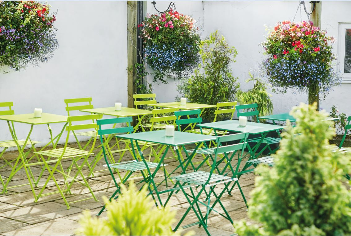 Outdoor patio with green patio chairs and tables surrounded by plants and flowers