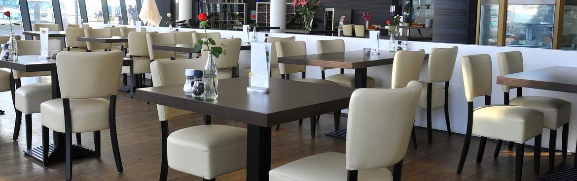 Restaurant with wooden tables and white upholstered dining chairs