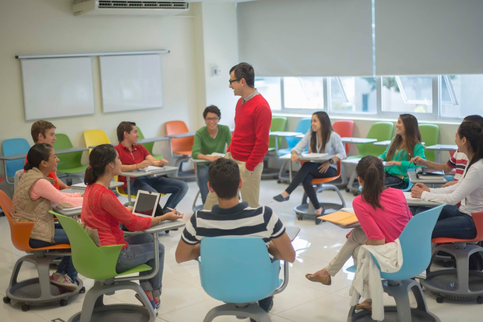 Male teacher standing in the centre of circle of students sitting in chair desks on wheels